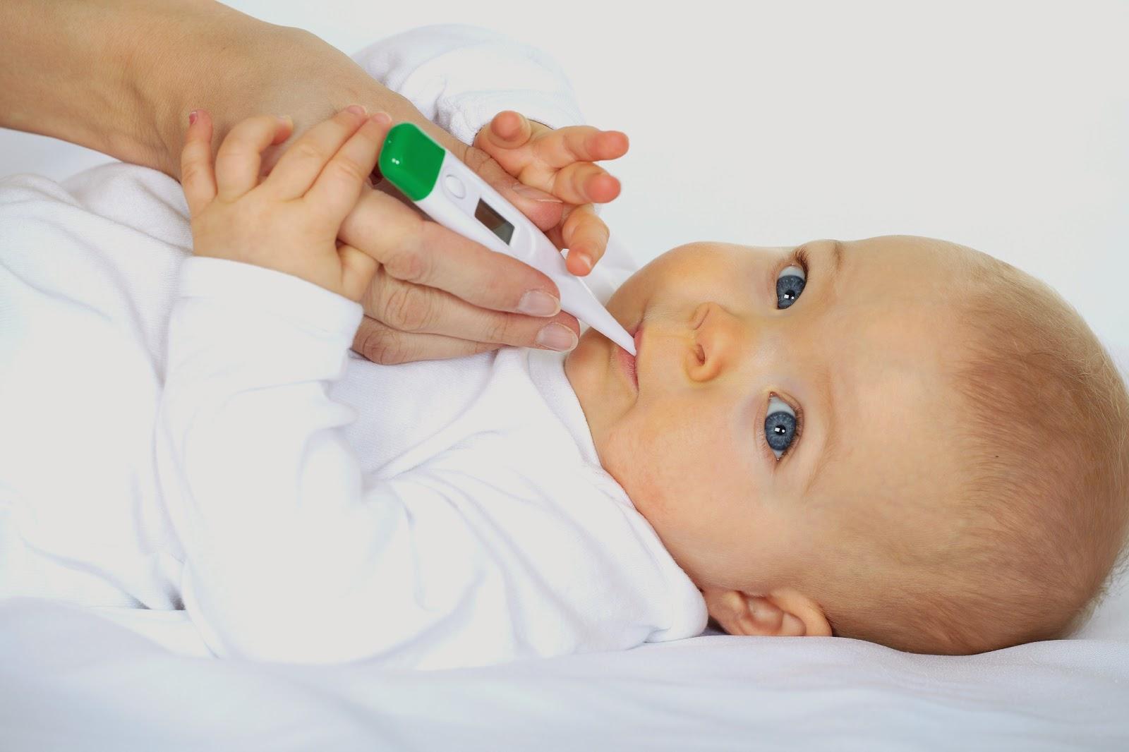 Dùng nhiệt kế để kiểm tra nhiệt độ cho trẻ